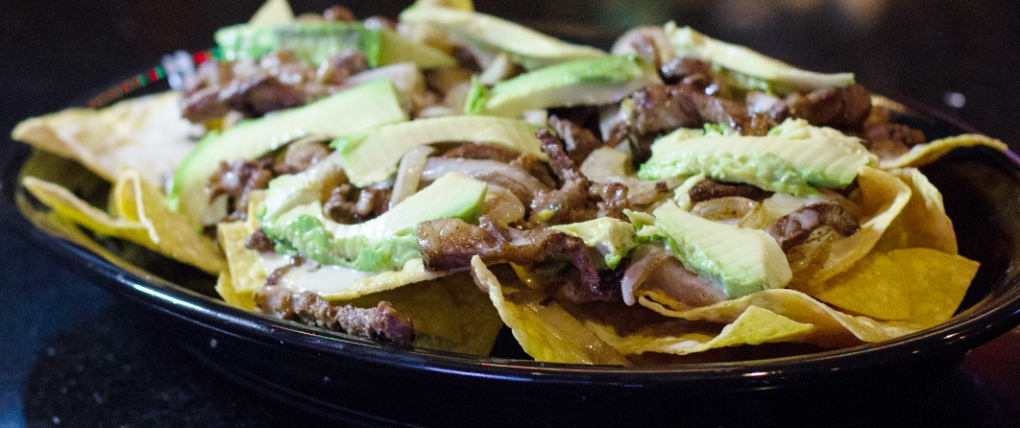 Nachos Vallarta – Grilled steak, sliced avocado, onions and topped with nacho cheese.